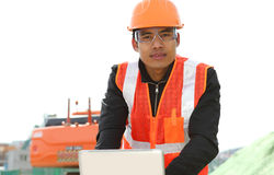 Road construction worker with  laptop. Road construction worker using laptop standing front excavator Stock Photos