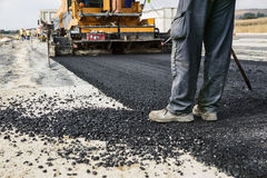 Road Construction. Worker operating asphalt paver machine during road construction and repairing works Royalty Free Stock Images