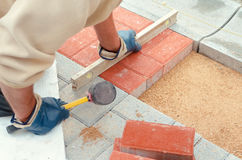 Road construction. Worker set up panel on the road with rubber hammer Royalty Free Stock Photos