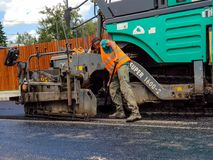 Road construction worker shoveling the hot asphalt. royalty free stock photos