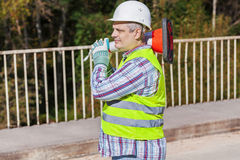 Road construction worker with traffic cone on the bridge. In summer day Royalty Free Stock Images