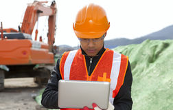 Road construction worker using laptop. Standing front excavator Royalty Free Stock Photo