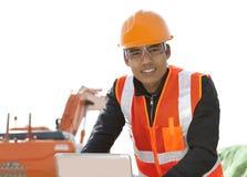 Road construction worker using laptop. Standing front excavator Stock Photo
