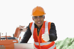 Road construction worker using laptop. Road construction worker with showing thumb up using laptop standing front excavator Royalty Free Stock Photos