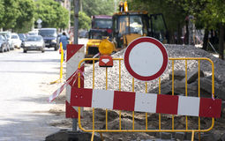 Road construction. Working machines and signs are seen in excavated street Royalty Free Stock Photos