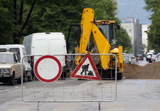 Road construction. Working machines and signs are seen in excavated street Stock Photo