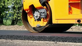 Close-up, Road construction works with roller compactor machine and asphalt finisher. Road roller laying fresh asphalt