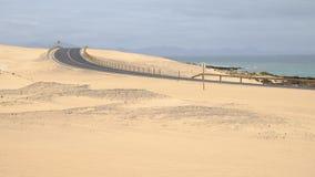 Road in Corralejo Dunes, Fuerteventura, Spain. Curved road in the Corralejo Dunes - the Natural Reserve on the Canary Island Fuerteventura, Spain Stock Images