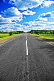 Road in countryside. Scenic view of straight road receding in Summery countryside with blue sky and cloudscape background Stock Photography