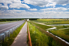 Road through countryside. Scenic view of road receding over bridge in green countryside with blue sky and cloudscape background, Murom, Russian Federation Royalty Free Stock Image