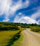 Road in countryside. Scenic view of road through green countryside with blue sky and cloudscape background Stock Photo