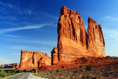 Road through Courthouse Towers, Arches National Park, Utah. The park road is dwarfed by the imposing Courthouse Towers at the end of the Avenue near the entrance stock photography