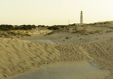 Road covered with sand from the dunes, road towards lighthouse of Trafalgar, Cadiz, Spain at sunset royalty free stock photography