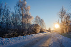 Road covered with snow in russian village in the sunset in wintertime Royalty Free Stock Images