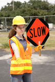 Road Crew Slow Sign. A female construction road crew member holding a slow sign for traffic stock image