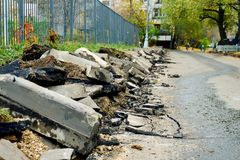 Broken freshly dug up old curbstones with pieces of an asphalt and earth lying on the road in Moscow. Road curb replacement on the Moscow street in Autumn royalty free stock photography