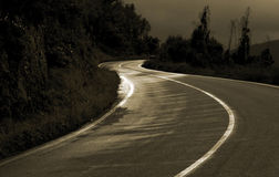 Road Curve. Sepia landscape of a s-curve in a mountain road with sun reflection Royalty Free Stock Photography