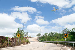 road curve and Airplane flying with blue sky background,for broc Stock Image