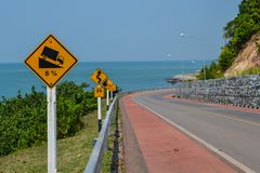 Road curve with caution signs and blue sea background Chanthabur. I Thailand Stock Photo