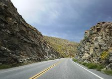 Road curve through mountains in california desert Stock Images