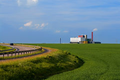 Road curve over fields and a factory Royalty Free Stock Image