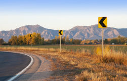 Road Curve Signs with Scenic Backdrop. Road curve signs in early morning golden light in autumn with scenic backdrop of the Flatirons Mountains in Boulder Royalty Free Stock Photos