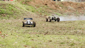 Road curve. Two remote controlled cars on dirty race track Royalty Free Stock Image