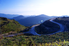 Road Curves at a Mountain. Landscape scene of road and mountains Royalty Free Stock Images