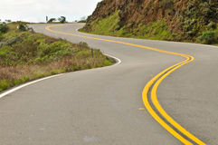 Road curves up a hill Stock Photography