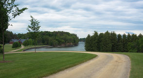 Road curving around to lake and barn Royalty Free Stock Photo