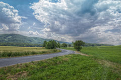 Road Curving Through Field Stock Photography