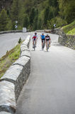Road cycling group. Friends by road cycle uphill Royalty Free Stock Images