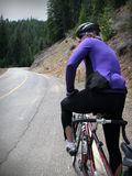 Road cyclist. In purple jersey resting on a steep mountain road climb Stock Photos