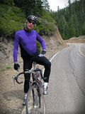 Road cyclist. In purple jersey resting on a steep mountain road climb Royalty Free Stock Photography