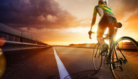 Road cyclist. Cyclist, ride on the road in mountain. Sunset landscape Royalty Free Stock Photography