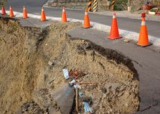 Road Damaged by Landslide. Red and white traffic cones mark a  road that has been damaged by a landslide Stock Images