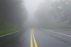 Road Danger Disappearing Into Fog. Wet road shown disappearing in dense fog.  Dangerous to drive in fog Stock Photos