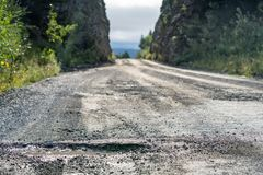 Giant pothole McCarthy Road from Chitina to McCarthy in Wrangell-St. Elias National Park. This road is dangerous, gravel road with potholes and railroad spikes royalty free stock image