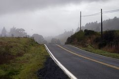 Road in dark fog. Highway 1 in Northern California crests a small hill into a rainstorm royalty free stock photography