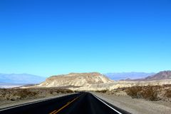 Road in the Death Valley National Park with blue sky background, California Royalty Free Stock Image