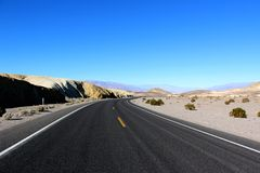 Road in the Death Valley National Park with blue sky background, California Stock Images