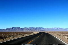 Road in the Death Valley National Park with blue sky background, California Stock Photo