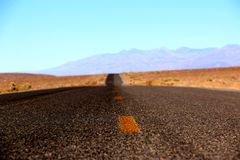 Road in the Death Valley National Park with colorful sky background, California Stock Images