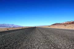 Road in the Death Valley National Park with colorful sky background, California Stock Photography