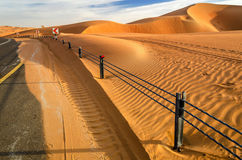 A road through a desert dunes. Taken in the Liwa Oasis, Abu Dhabi area, United Arab Emirates Royalty Free Stock Image