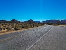 Road through the desert of the Joshua Tree Park in California. View over the road running through the desert landscape of the Joshua Tree Park in California Royalty Free Stock Photography