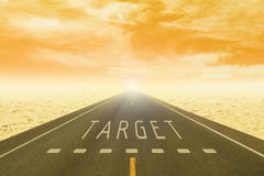 Road through the desert with sign target on asphalt at sunset Stock Image