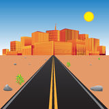 Road in the desert with view of the city skyline.  Royalty Free Stock Photography