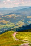 Road down the grassy hill in to the valley. Beautiful mountainous landscape. wonderful place for walking, hiking, riding and other activities Stock Photos