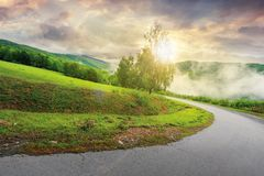 Road down the hill at sunrise. Sun light come through the tree. cloudy sky above the distant mountain ridge. mysterious foggy weather royalty free stock photos